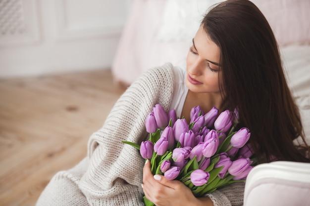 Piękna kobieta z kwiatami w pomieszczeniu
