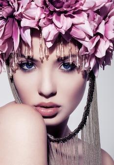Piękna kobieta z kwiatową koroną i makijażem trzyma rękę pod brodą z ramieniem z przodu