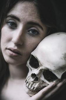 Piękna kobieta z ludzką czaszką
