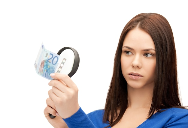 Piękna kobieta z lupą i gotówką w euro