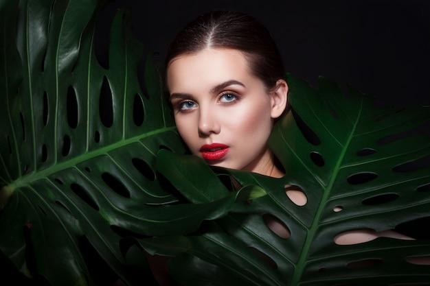 Piękna kobieta z makijażem i czerwonymi wargami w zielonych liściach