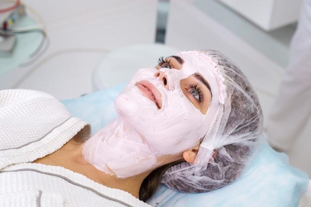 Piękna kobieta z maseczka na twarz w salonie kosmetycznym