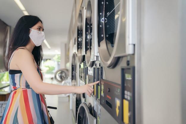 Piękna kobieta z maską robi pralni przy laundromat sklepem.
