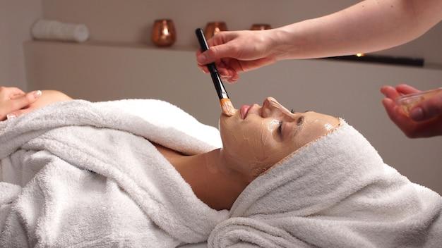 Piękna kobieta z maską twarzy w salonie kosmetycznym. stosowanie maski na twarz kobiety w salonie kosmetycznym. terapia spa dla młodej kobiety otrzymującej maskę na twarz w salonie kosmetycznym. kosmetyczka robi maskę na twarz
