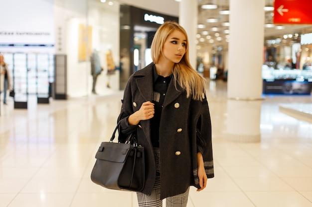 Piękna kobieta z modną torbą w modnym stylowym płaszczu w centrum handlowym