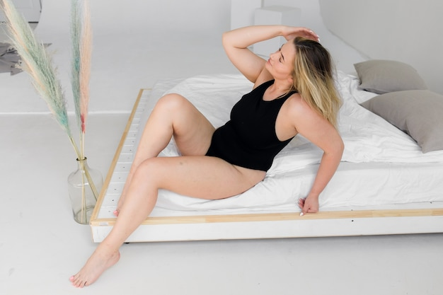 Piękna kobieta z nadwagą w czarnym stroju kąpielowym na białej ścianie