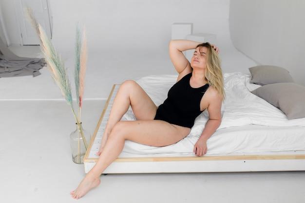 Piękna kobieta z nadwagą w czarnym stroju kąpielowym na białym tle