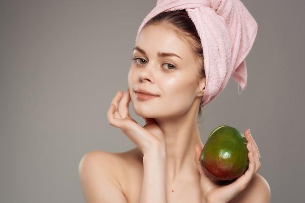 Piękna kobieta z nagim ciałem po prysznicu egzotycznym na białym tle
