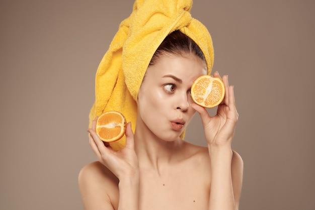 Piękna kobieta z nagim ciałem z czystą skórą mandarynki w dłoni