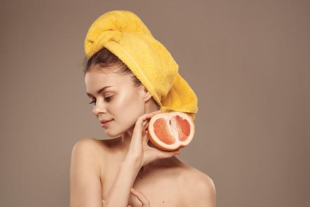 Piękna kobieta z nagim ciałem z owocowymi witaminami pozuje zbliżenie