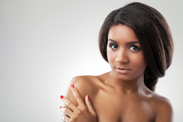 Piękna kobieta z nagimi ramionami dotyka jej ramienia