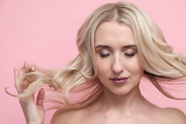 Piękna kobieta z nagimi ramionami na pastelowym różowym tle