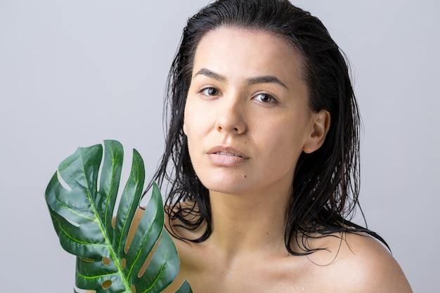 Piękna kobieta z naturalnych zielonych liści palmowych portret. moda, uroda, makijaż, kosmetyki.