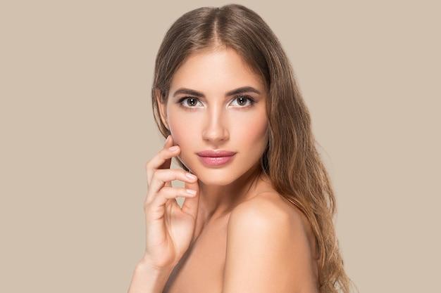 Piękna kobieta z naturalnym makijażem dorywczo codzienny kosmetyk dotyka jej twarzy. kolor tła brązowy