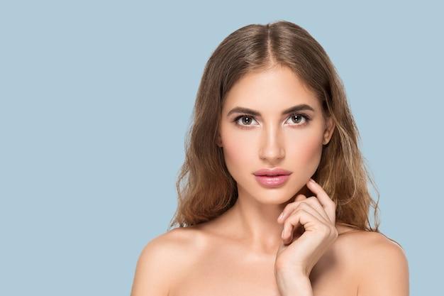 Piękna kobieta z naturalnym makijażem dorywczo codzienny kosmetyk dotyka jej twarzy. kolor tła niebieski