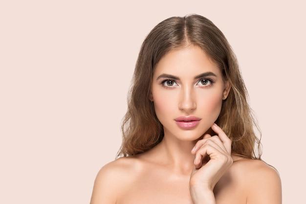 Piękna kobieta z naturalnym makijażem dorywczo codzienny kosmetyk dotyka jej twarzy. kolor tła różowy