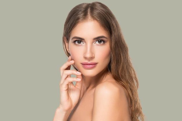 Piękna kobieta z naturalnym makijażem dorywczo codzienny kosmetyk dotyka jej twarzy. kolor tła zielony