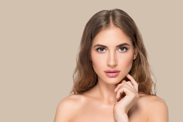 Piękna kobieta z naturalnym makijażem dorywczo codzienny kosmetyk dotyka jej twarzy. kolor tła