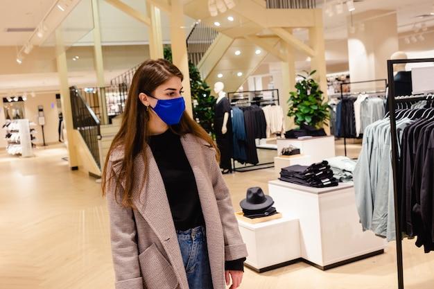 Piękna kobieta z niebieską maską robi zakupy w centrum handlowym