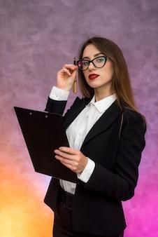 Piękna kobieta z ofertą schowka podpisuje umowę za pomocą pióra
