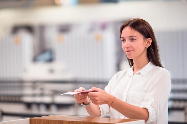 Piękna kobieta z paszportami i kartami pokładowymi w recepcji na lotnisku