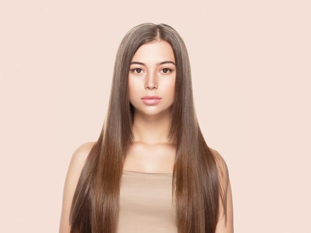 Piękna kobieta z piegami o zdrowej skórze i włosach długo gładka brunetka koncepcja fryzury na beżu