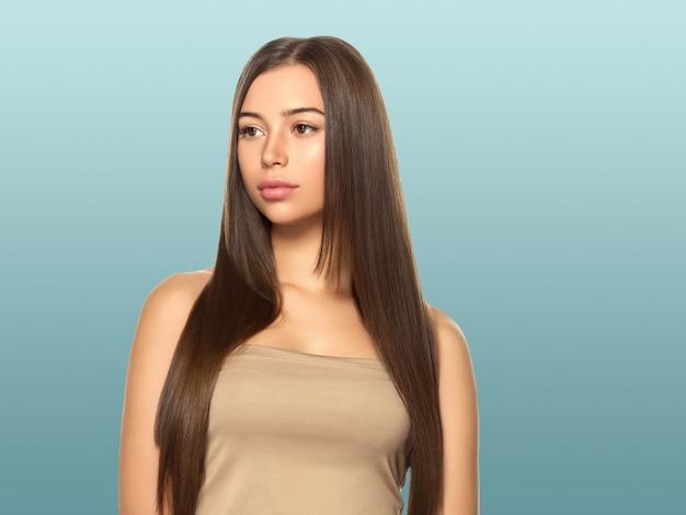Piękna kobieta z piegami o zdrowej skórze i włosach długo gładka brunetka koncepcja fryzury na niebiesko
