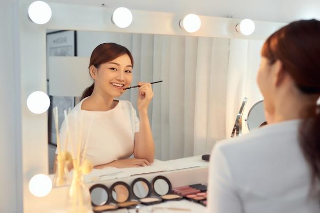 Piękna kobieta z piękna twarz, stosowanie balsamu do ust, szminka trzymać na. koncepcja kosmetyki do pielęgnacji ust.