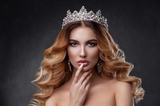 Piękna kobieta z pięknym kolorem makijażu, korona na głowie.