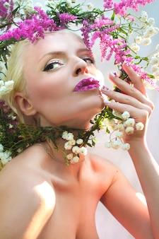 Piękna kobieta z projektem letniego różowego kwiatu astilbe na ustach i palcach