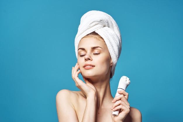 Piękna kobieta z ręcznikiem na głowie masażer w dłoniach do pielęgnacji skóry