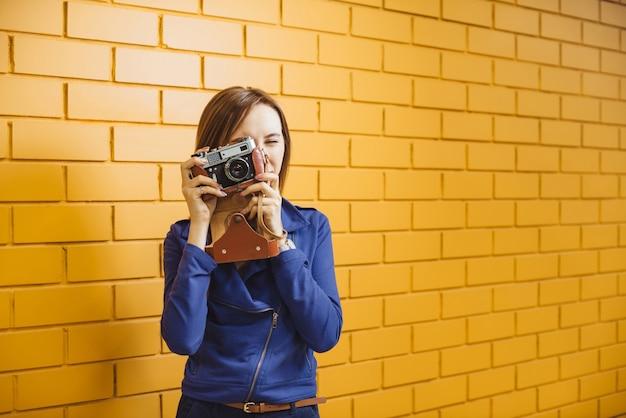 Piękna kobieta z retro filmową photocamera na żółtym murem