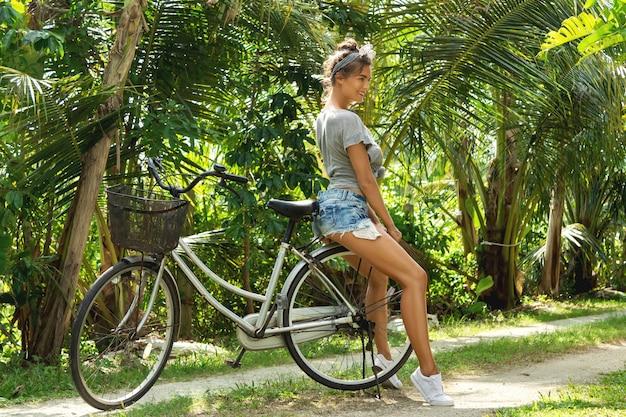 Piękna kobieta z rowerem w tropikalnym ogrodzie