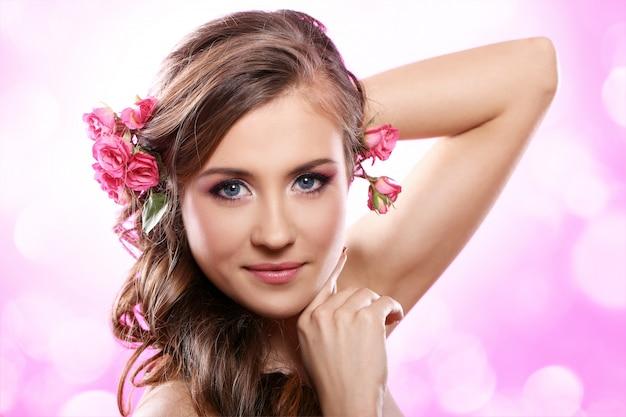 Piękna kobieta z różami we włosach