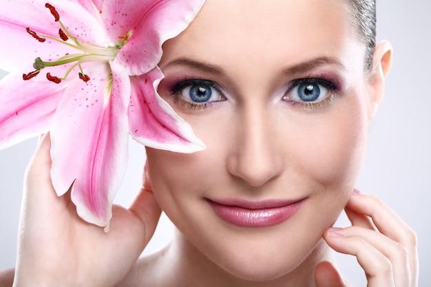 Piękna kobieta z różowym leluja kwiatem