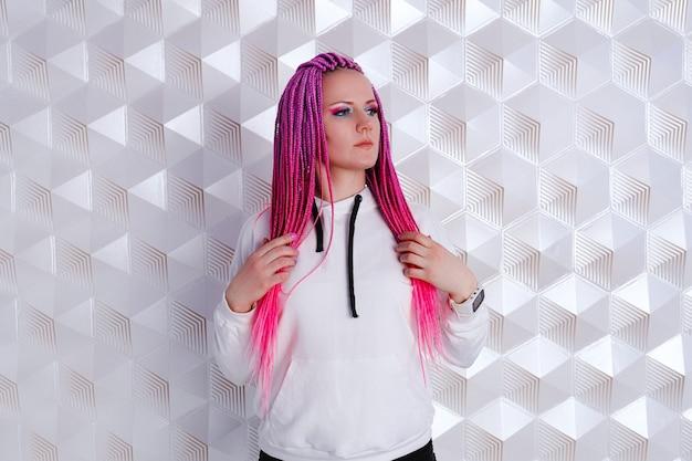 Piękna kobieta z różowymi włosami w białej bluzie z kapturem na futurystycznym tle. gra rzeczywistości rozszerzonej, technologia przyszłości, koncepcja ai. vr.