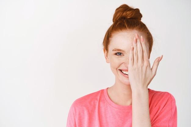 Piękna kobieta z rudymi włosami i niebieskimi oczami zakrywającymi połowę twarzy, uśmiechnięta z przodu, stojąca bez makijażu na białej ścianie