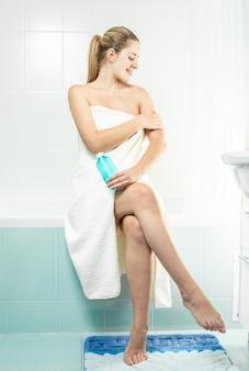 Piękna kobieta z seksownymi nogami używająca balsamu nawilżającego po prysznicu