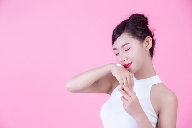 Piękna kobieta z śmietanką na skórze na różowym tle.