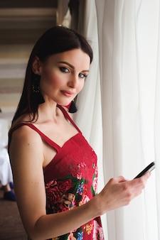 Piękna kobieta z telefonem komórkowym okno.