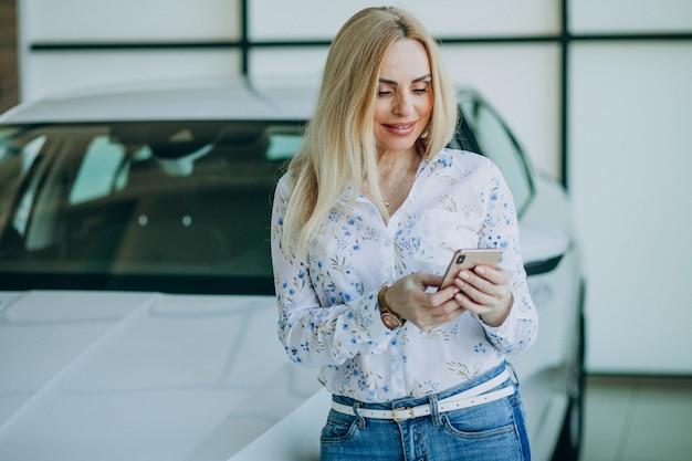 Piękna kobieta z telefonem w samochodowej sala wystawowej