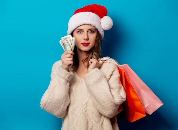 Piękna kobieta z torba na zakupy i pieniądze zegarem na błękit ścianie