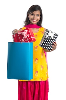 Piękna kobieta z torby na zakupy i pudełka na prezent na białym tle.