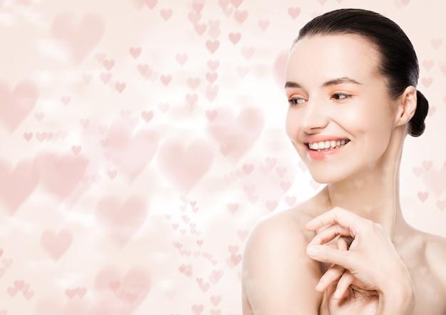 Piękna kobieta z uroczym uśmiechem naturalny makijaż spa pielęgnacja skóry portret różowy bokeh serce miłość białe tło