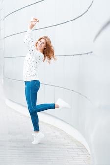 Piękna kobieta z uśmiechem w biały sweter, niebieskie dżinsy i białe trampki