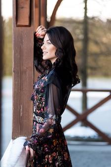 Piękna kobieta z uśmiechem w sukni w pobliżu drewnianej poręczy