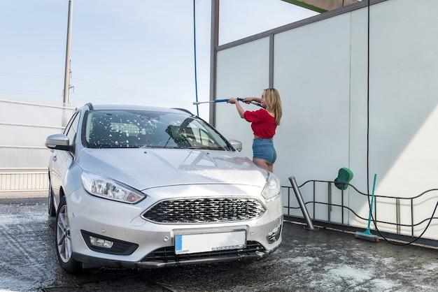 Piękna kobieta z węża wysokociśnieniowego nakłada mydlaną piankę na swój samochód