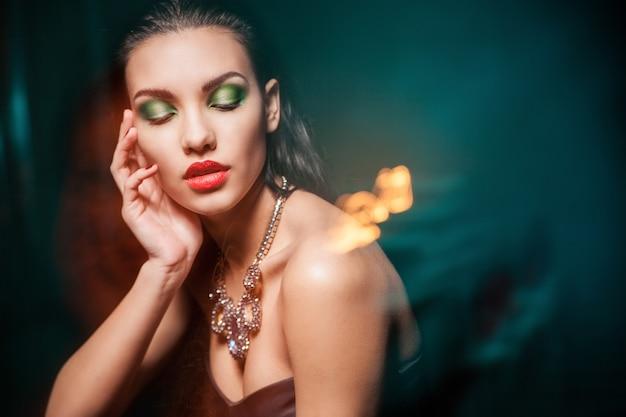 Piękna kobieta z wieczorowym makijażem na ciemnym tle. biżuteria i piękno. fotografia mody