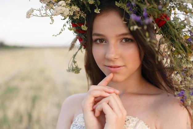Piękna kobieta z wieńcem na głowie siedzi w polu w kwiatach. pojęcie piękna, wolnego życia i naturalności