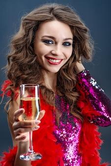 Piękna kobieta z zadowoleniem uśmiecha się podnoszący szkło szampan